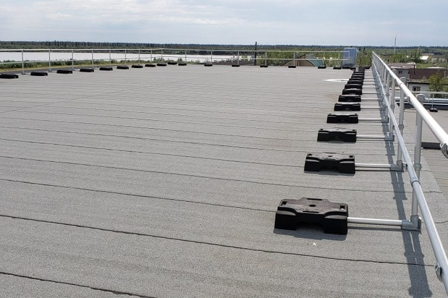 The perimeter of a roof without parapet protected by a fall protection system made of aluminum tubing and rubber counterweights