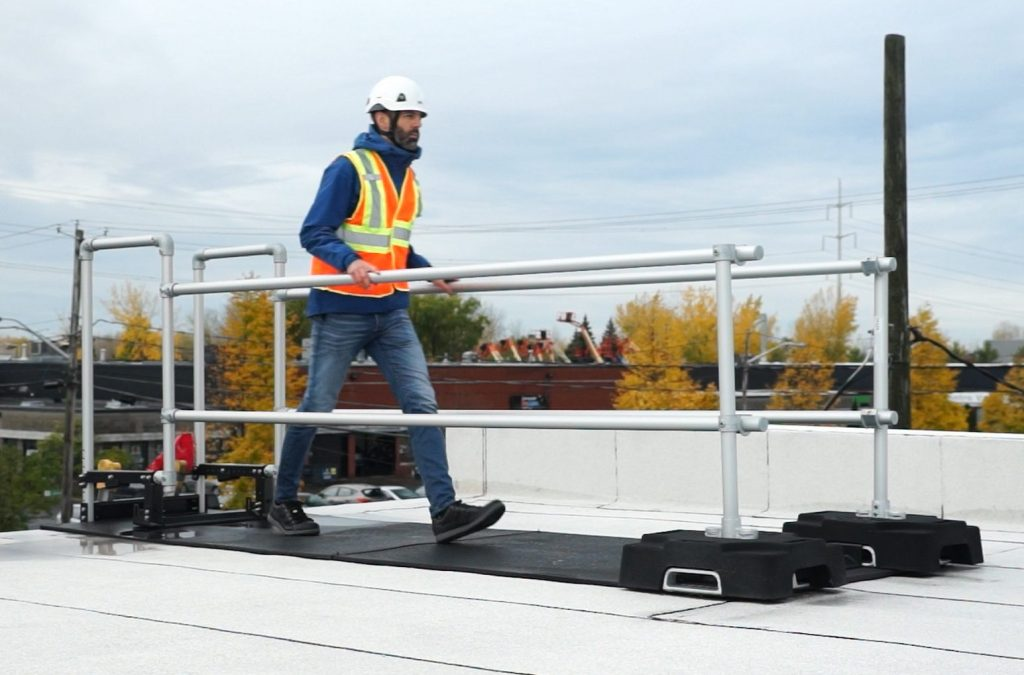 A worker make his way trough the ladder stabilizer guardrail