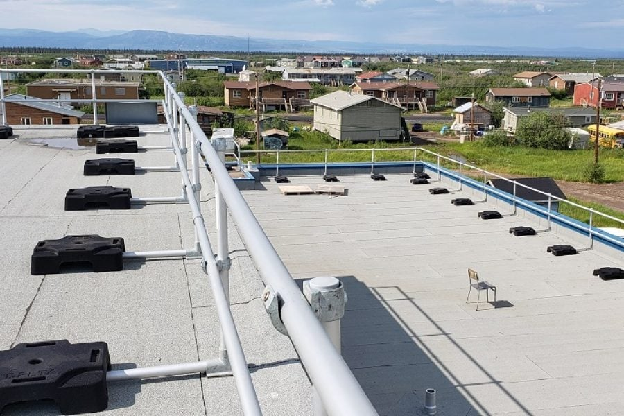 Freestanding guardrail on a roof with parapet. Railing made from aluminum tubing and rubber counterweights on two floors