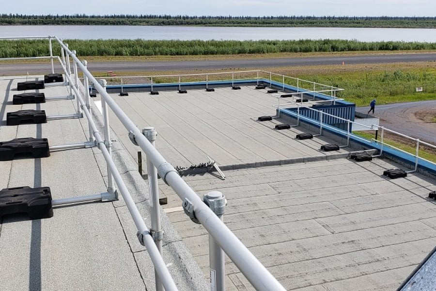 Freestanding guardrail on a roof with parapet. Railing made from aluminum tubing and rubber counterweights
