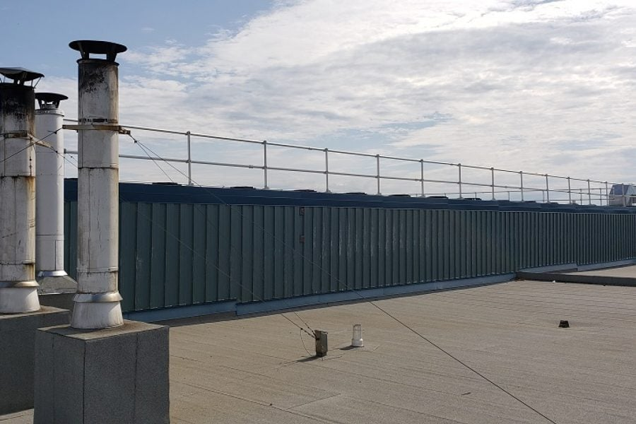 Freestanding guardrails on a roof without a parapet. Railing made of aluminum tubing and rubber counterweights on a second floor