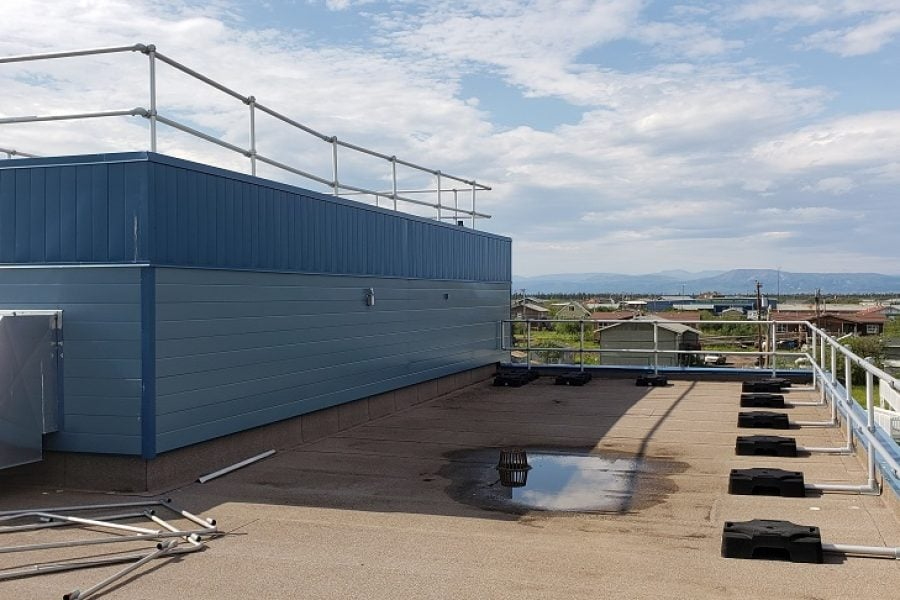 Freestanding guardrail on a roof with parapet. Railing made of aluminum tubing and rubber counterweights on two floors