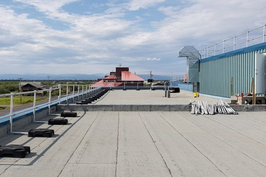 Freestanding guardrails on a roof with parapet. Railing made of aluminum tubing and rubber counterweights on two floors