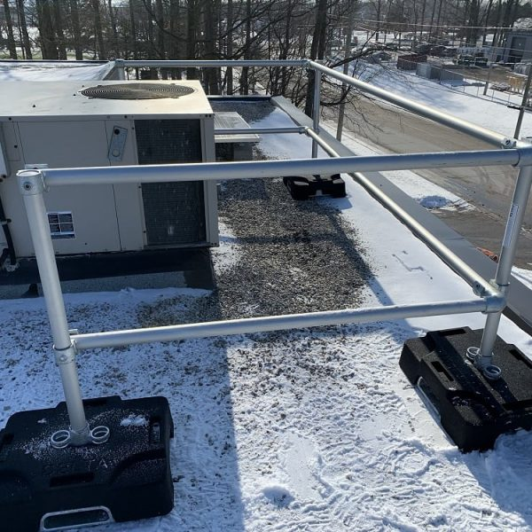 Rooftop safety railing protection working along HVAC unit on roof
