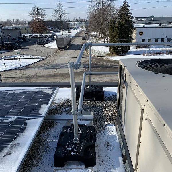 Rooftop guardrail installed around mechanical equipment on roof in winter