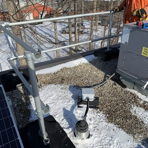 Installation of a rooftop safety railing in Ontario during cold condition