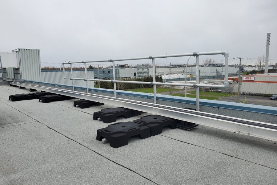 freestanding guardrails on a flat rooftop with parapet. VSS Classic configuration with rubber counterweights and aluminum tubing.