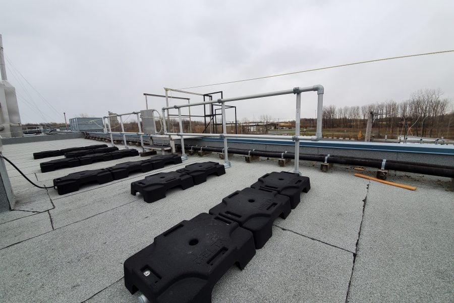 freestanding ladder fall protection system on rooftop with parapet. VSS Classic configuration with rubber counterweights and aluminum tubing