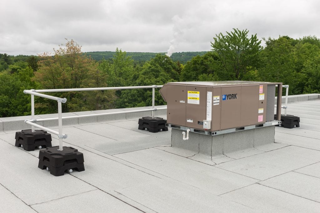 Freestanding guardrail system on a flat roof to protect HVAC component