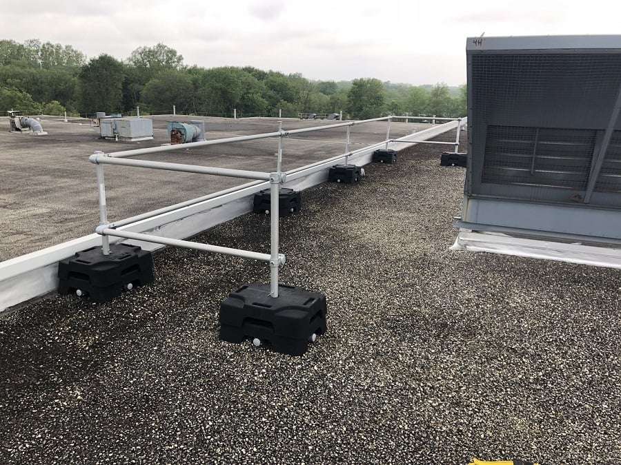 Freestanding guardrail installed on a roof with parapet. VSS Compact configuration with rubber counterweight and aluminum tubing to protect HVAC component