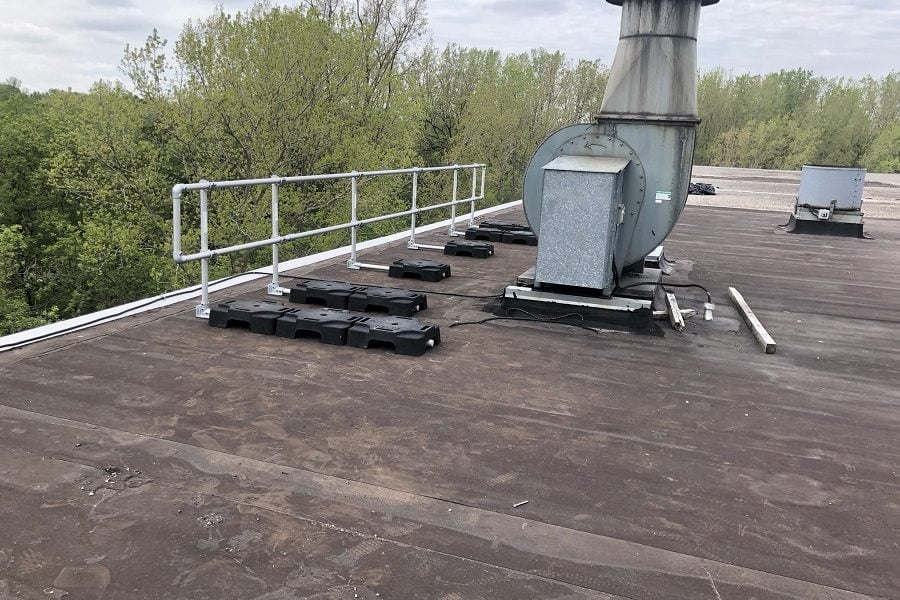 Freestanding guardrail installed on a roof with parapet. VSS Classic configuration with rubber counterweight and aluminum tubing to protect HVAC component