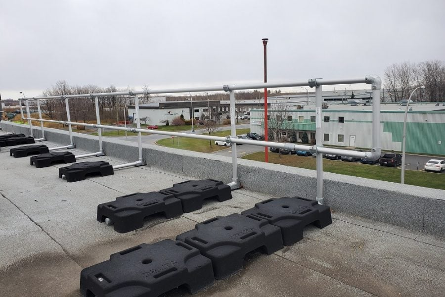 freestanding guardrails on rooftop with parapet. VSS Classic configuration with rubber counterweights and aluminum tubing