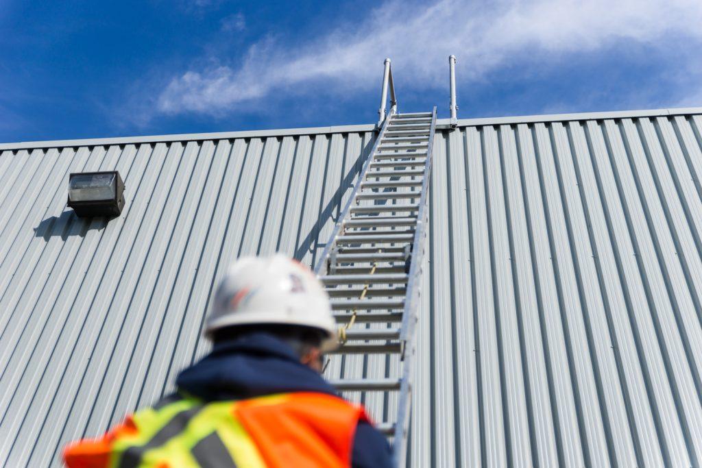 Travailleur devant une échelle posée le long du mur d'un bâtiment
