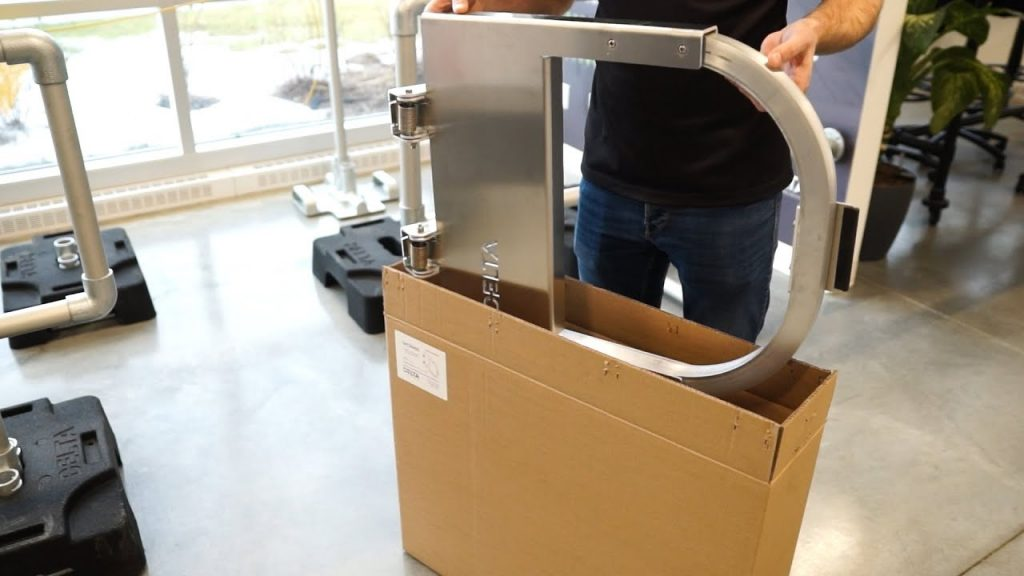 Man unpacking aluminum self-closing safety gate from original box