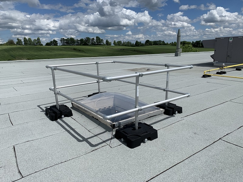 Fall protection system installed around a rooftop skylight