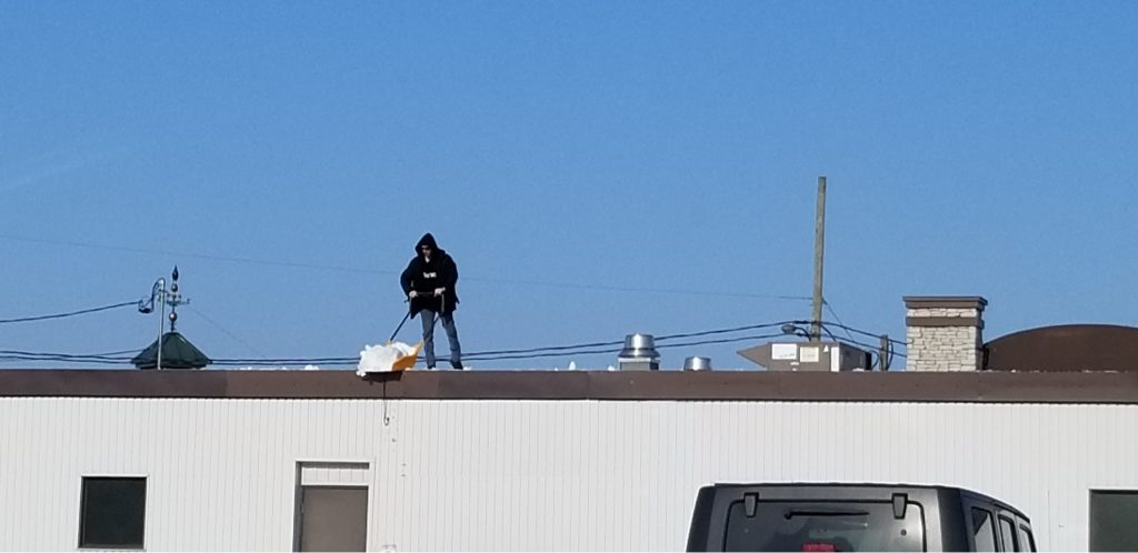 Man on roof doing snow removal without protection